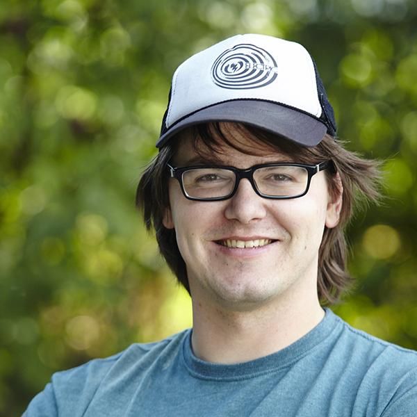 Porträt eines jungen Mannes mit Brille und Kappe.