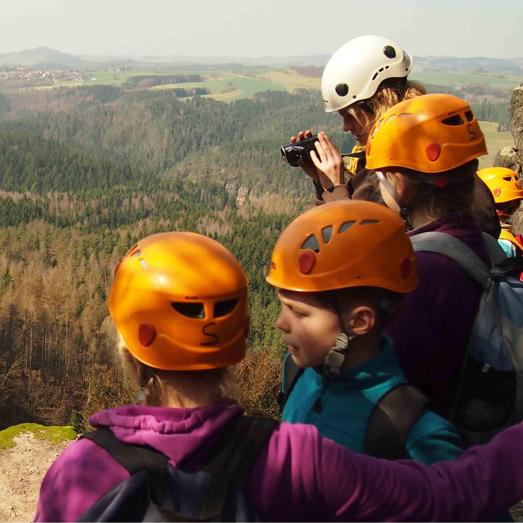 Mehrere Kinder stehen auf einem Berg. Im Hintergrund sieht man das Tal und Wälder. Inklusive Kletterreise des Indiwi Berlins.