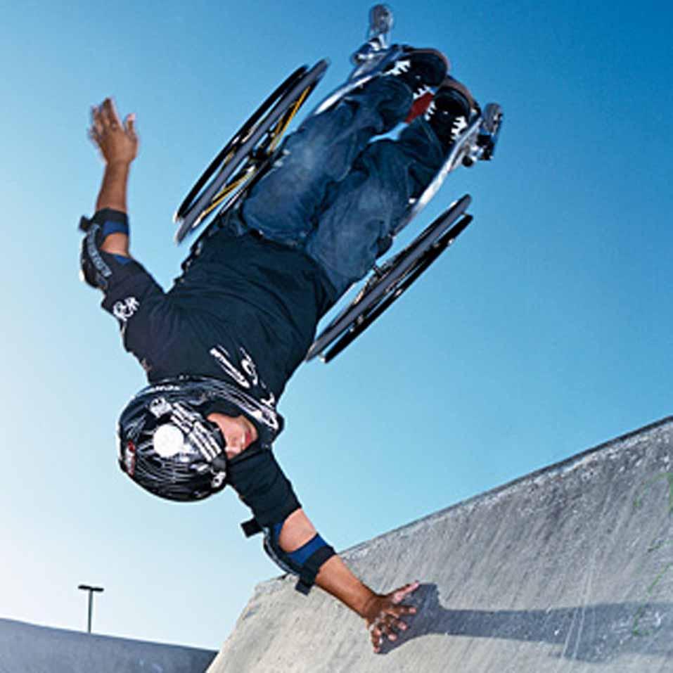 Rollstuhlfahrer springt in der Luft über eine Halfpipe.
