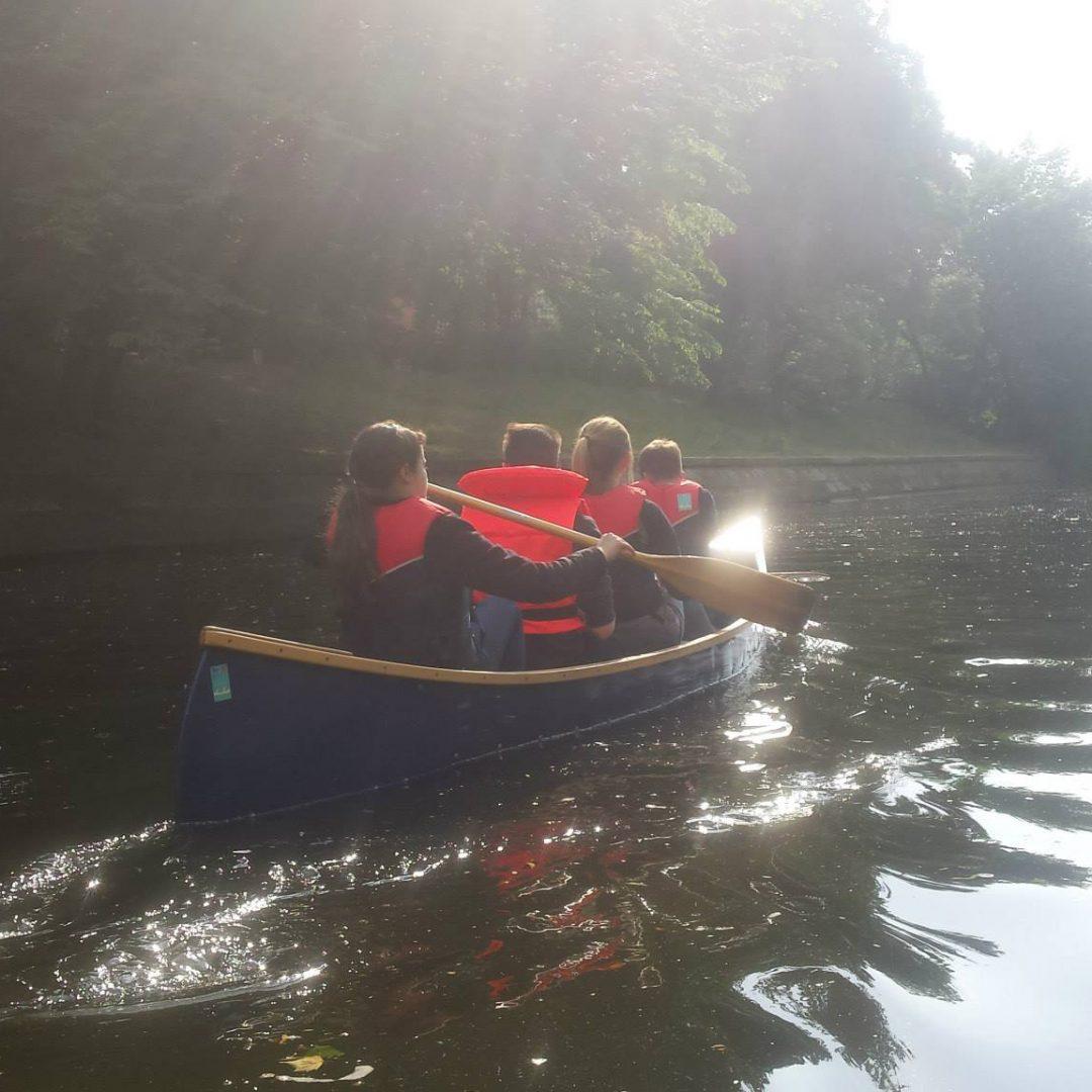 Vier Kinder padeln in einem blauen Kanu über den See. Inklusive Stadtcamper des Indiwi Berlins.