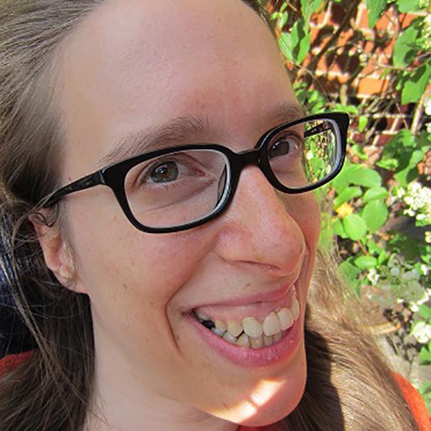 Porträt von einer lächelnden Frau mit Brille.