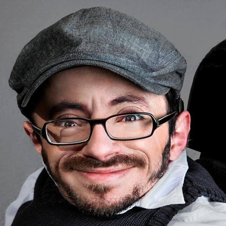 Porträt von einem jungen Mann mit Bart und Brille.