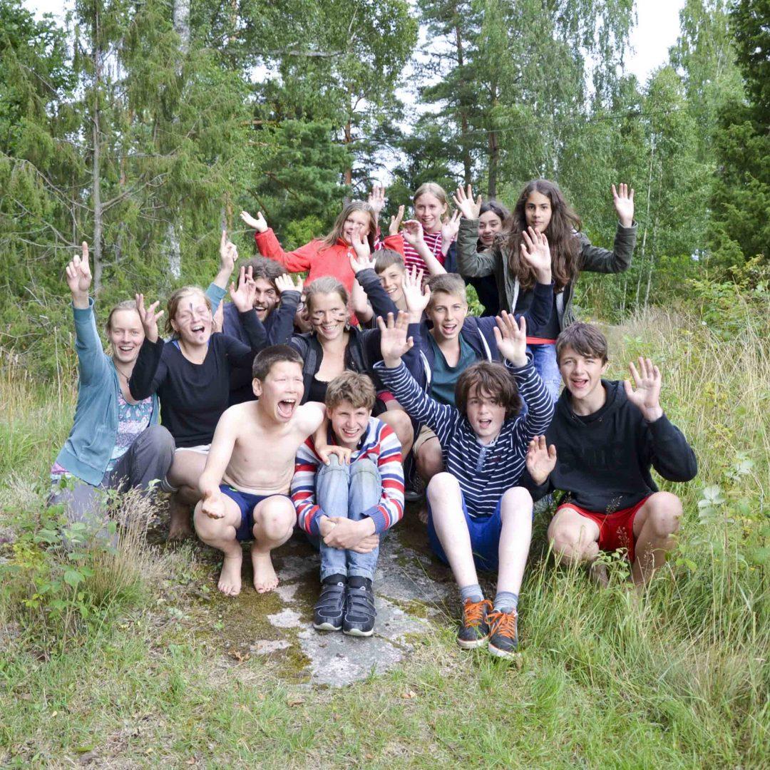 Eine Gruppe mit Kindern und Jugendlichen sitzen auf der Wiese. Einige strecken die Hände in die Luft. Inklusive Sommerreise des Indiwi Berlins.