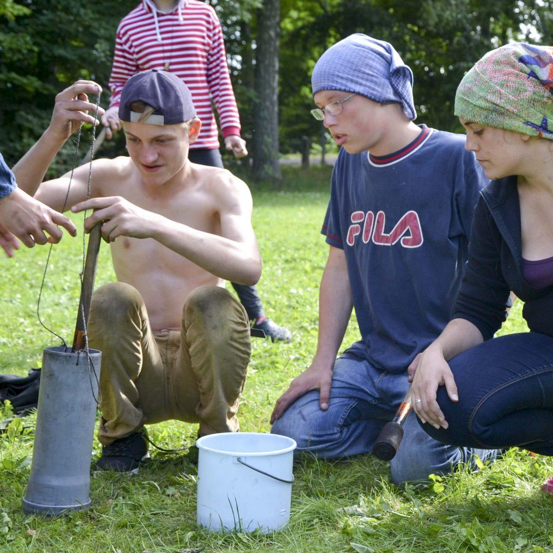 Drei Jugendliche hocken auf der Wiese vor zwei Eimern. Inklusive Sommerreise des Indiwi Berlins.