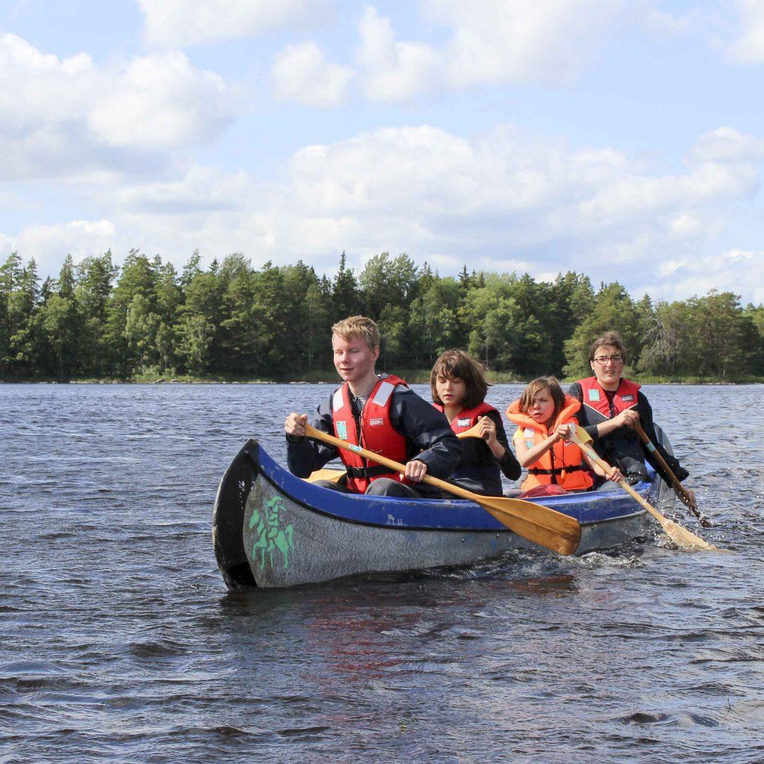 Vier Kinder padeln zusammen in einem blauen Kanu auf dem Wasser. Im Hintergrund sind Bäume. Inklusive Sommerreise des Indiwi Berlins.