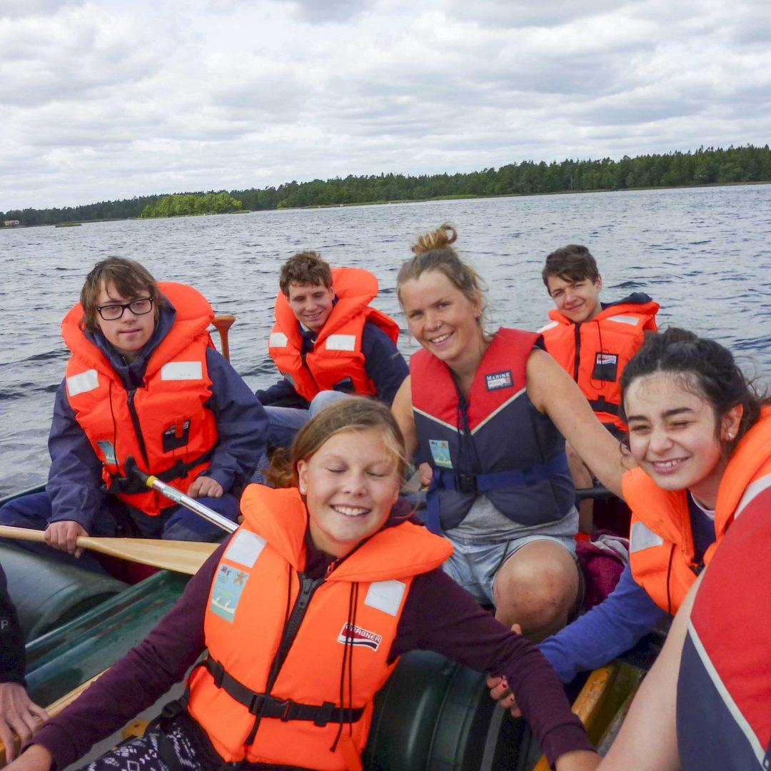 Kleine Gruppe mit Kindern und Jugendlichen sitzen in Booten. Sie tragen Schwimmwesten. Im Hintergrund sieht man das Wasser. Inklusive Sommerreise des Indiwi Berlins.