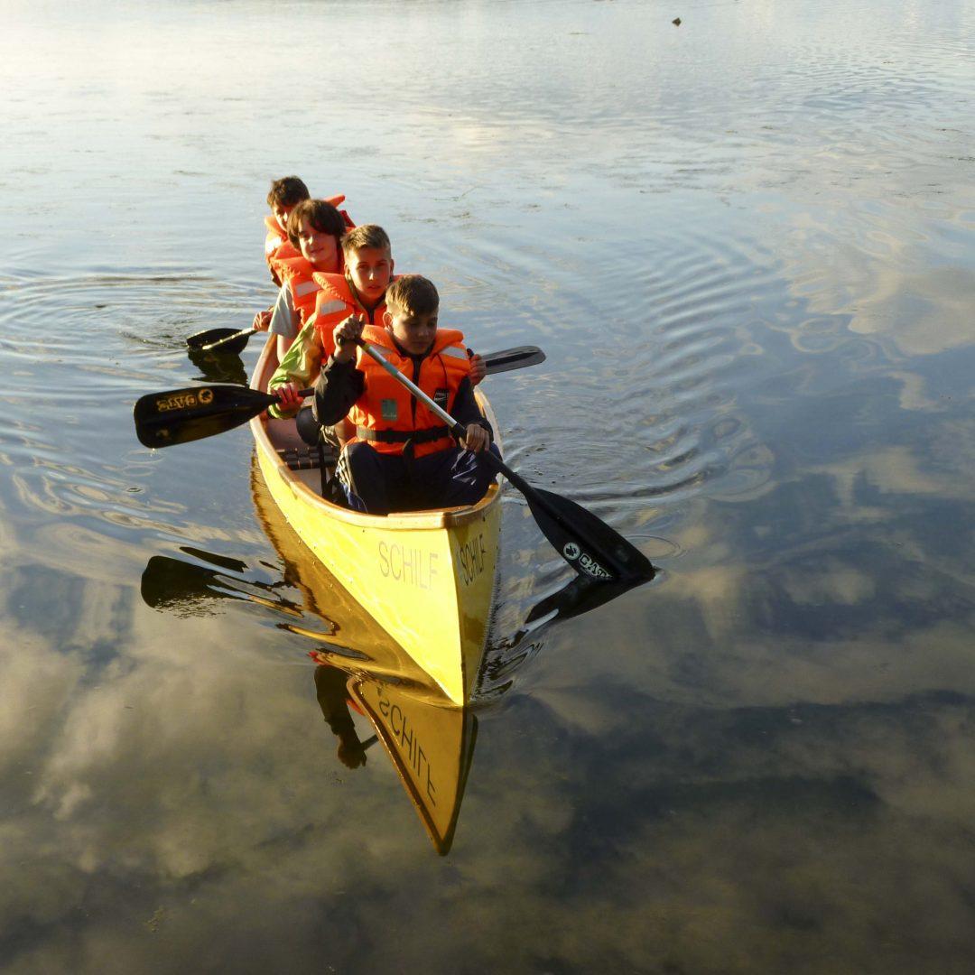 Vier Kinder mit Schwimmweste padeln mit einem gelben Kanu über den See. Inklusive Sommerreise des Indiwi Berlins.