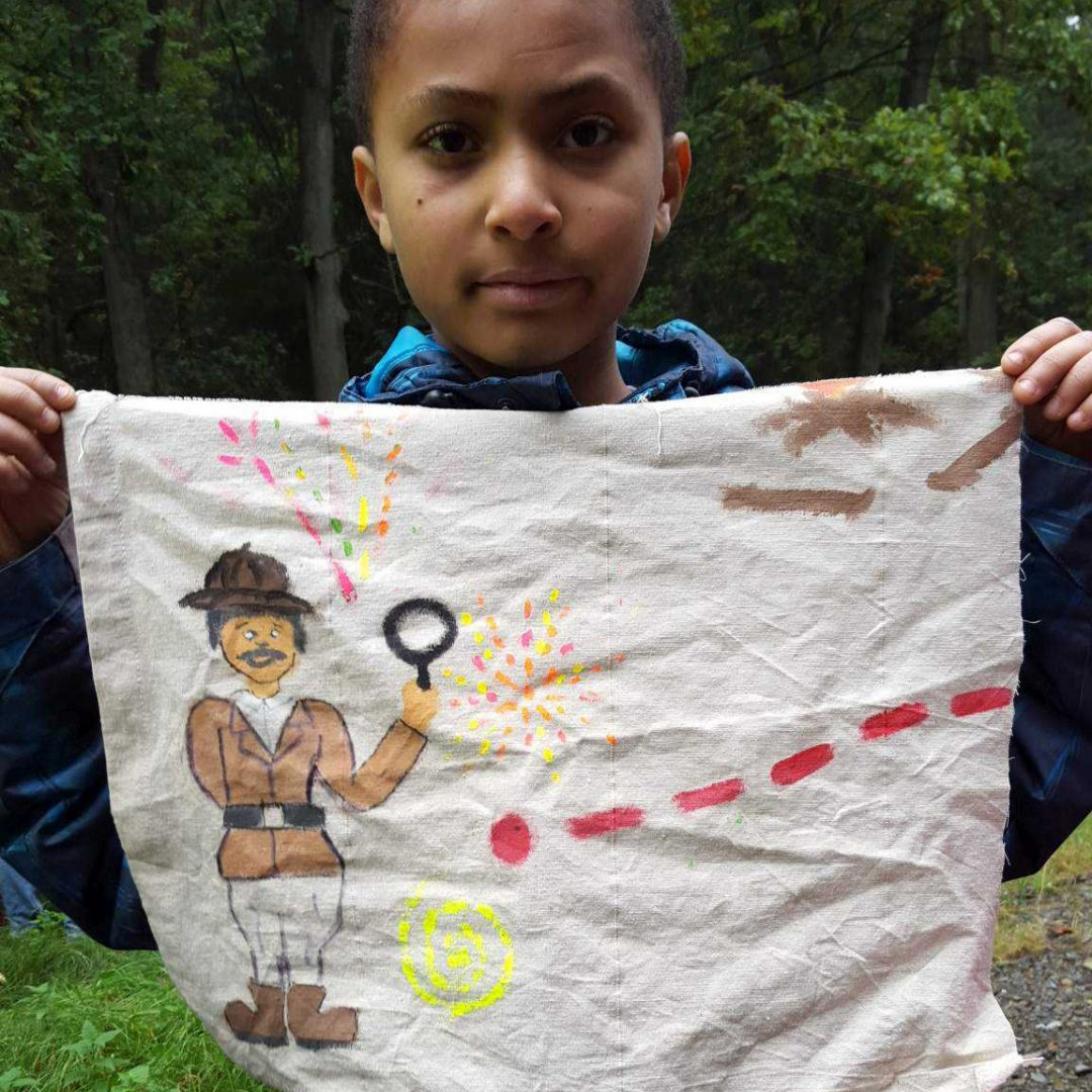 Porträt eines Jungen auf der inklusiven Herbstreise des Indiwi Berlins. Er hält ein bemaltes Tuch in seinen Händen.