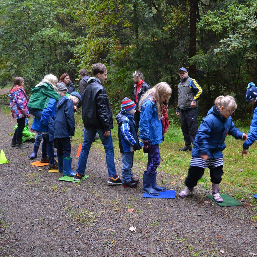Mehrere Kinder der inklusiven Herbstreise des Indiwi Berlins stehen nebeneinander. Sie stehen mit den Füßen auf farbigen, rechteckigen Matten.