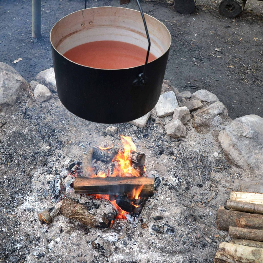 Ein Topf hängt über dem Lagerfeuer. Inklusive Herbstreise des Indiwi Berlins.