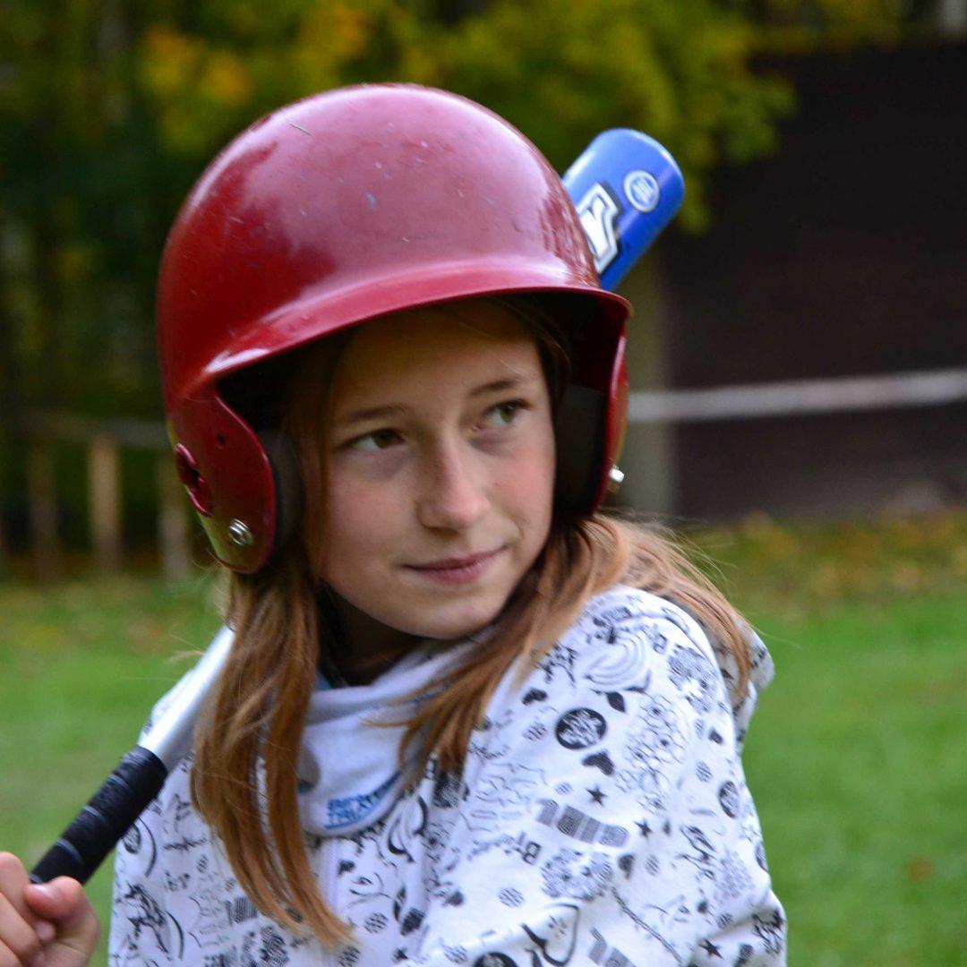 Porträt von einem Mädchen mit Helm und Baseballschläger. Inklusive Herbstreise des Indiwi Berlins.