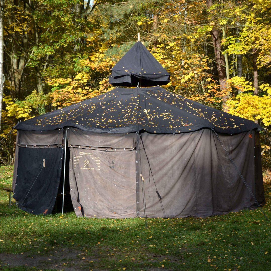 Große, schwarze Jurte auf einer Wiese. Im Hintergrund sind Bäume. Inklusive Herbstreise des Indiwi Berlins.