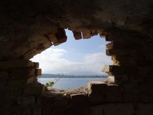 Loch in Felswand. Im Hintergrund Wasser.