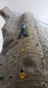 Kind klettert an einer Kletterwand. Inklusive Stadtcamper des Indiwi.