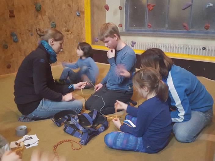 Kinder und Erwachsene sitzen vor einer Boulderwand. Inklusive Stadtcamper des Indiwi Berlins.