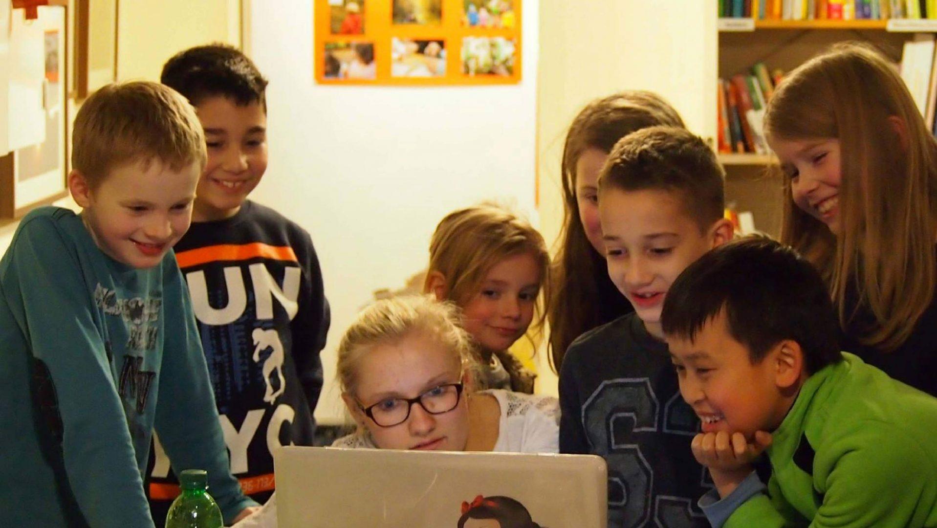 Mehrere Kinder stehen um einen Laptop herum. Sie lachen. Inklusives Medienprojekt des Indiwi Berlins.